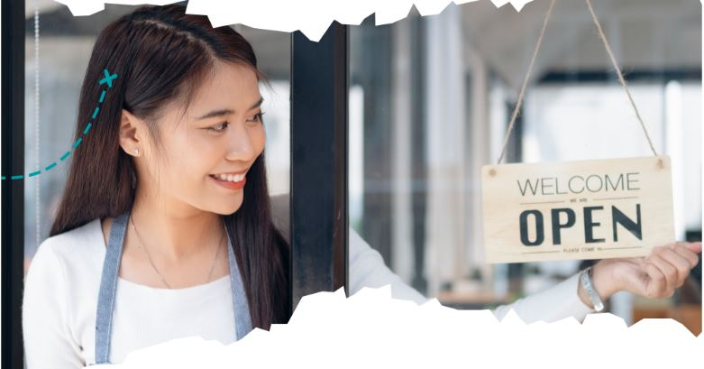 A young woman business owner smiling as she opens her business.